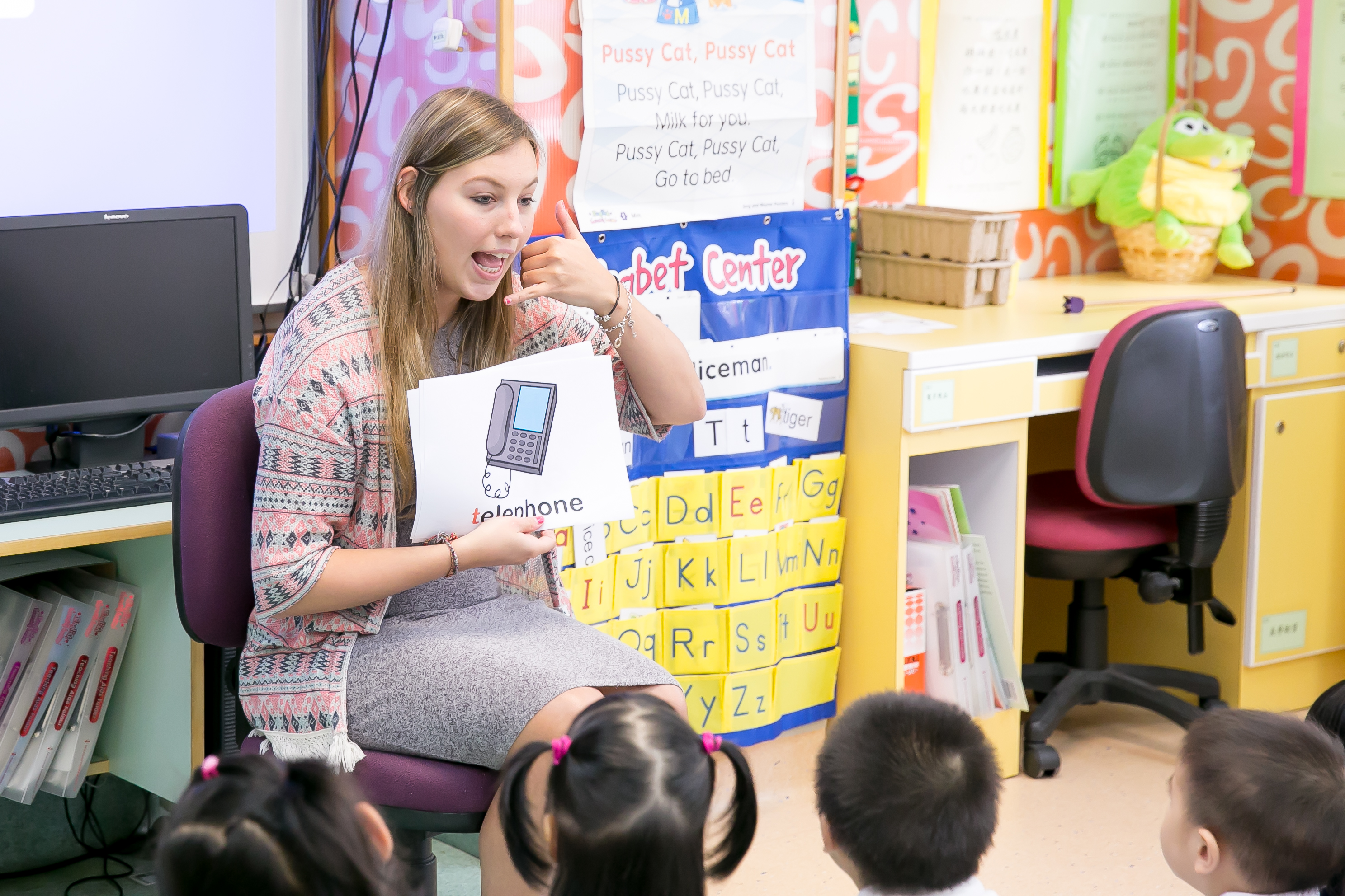 a TEFL teacher is explaining a telephone flashcard to chinese children