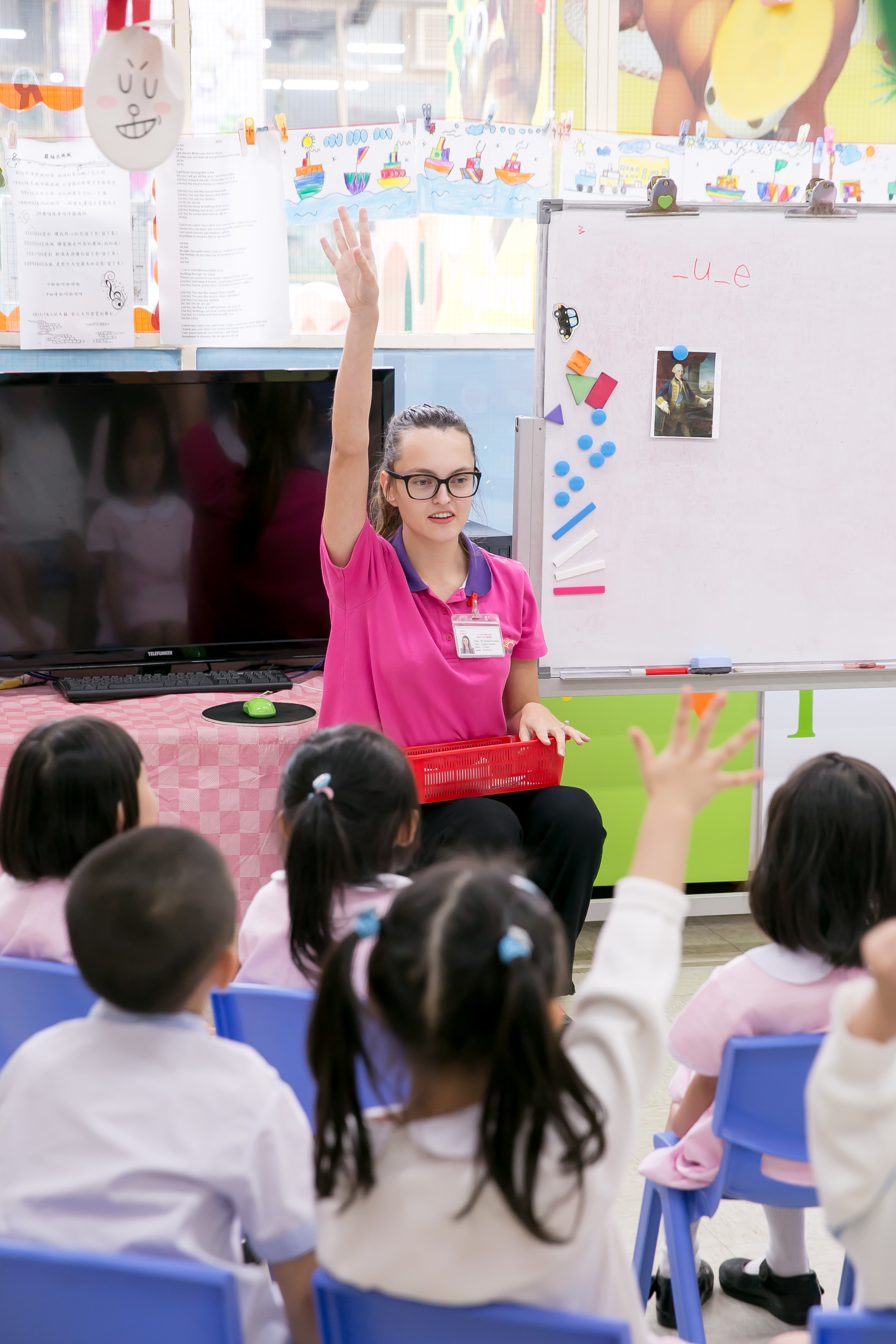 a TEFL teacher in pink t-shirt is encouraging children to participate in the lesson