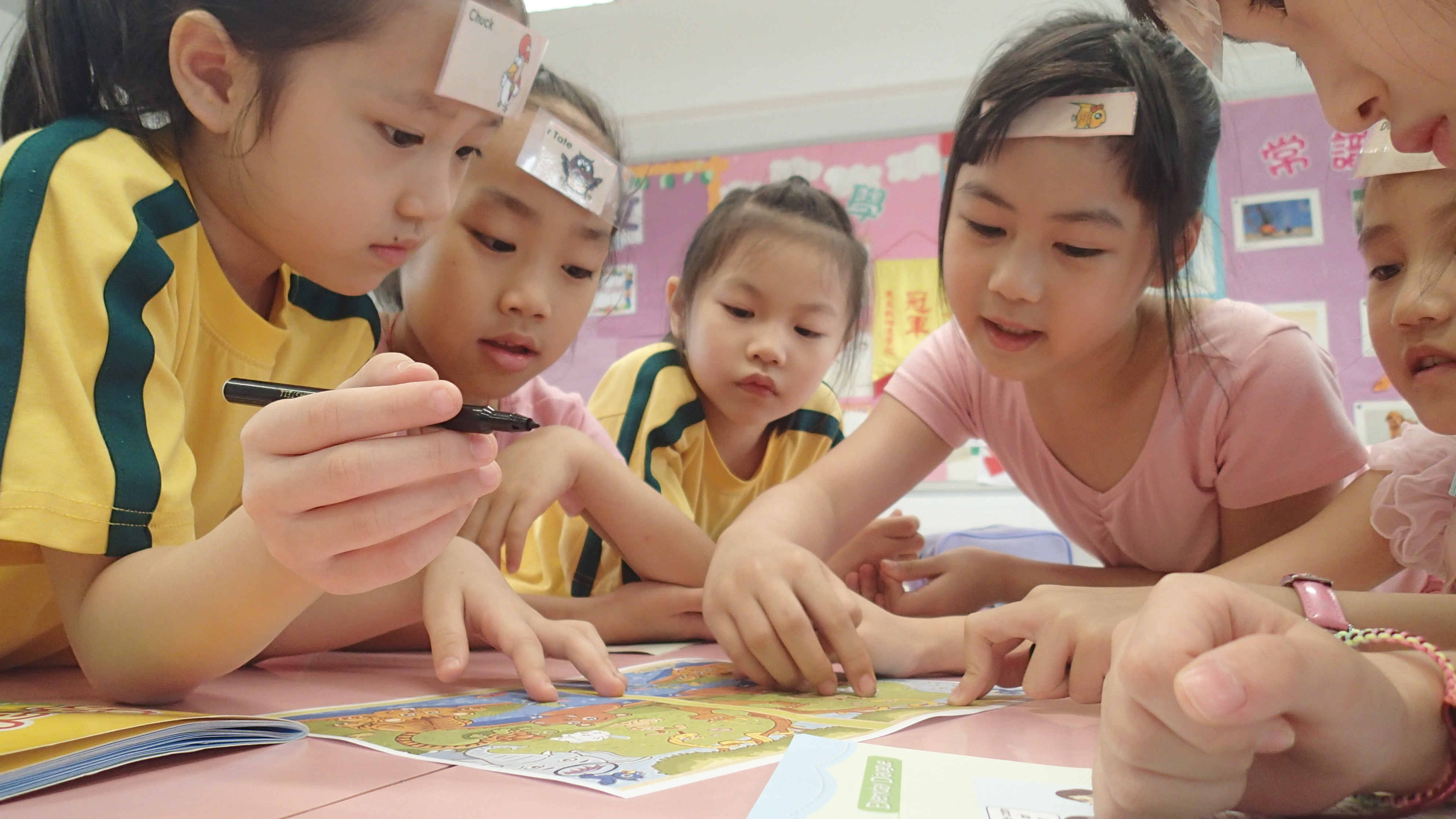 TEFL kindergarten students are playing at the desk